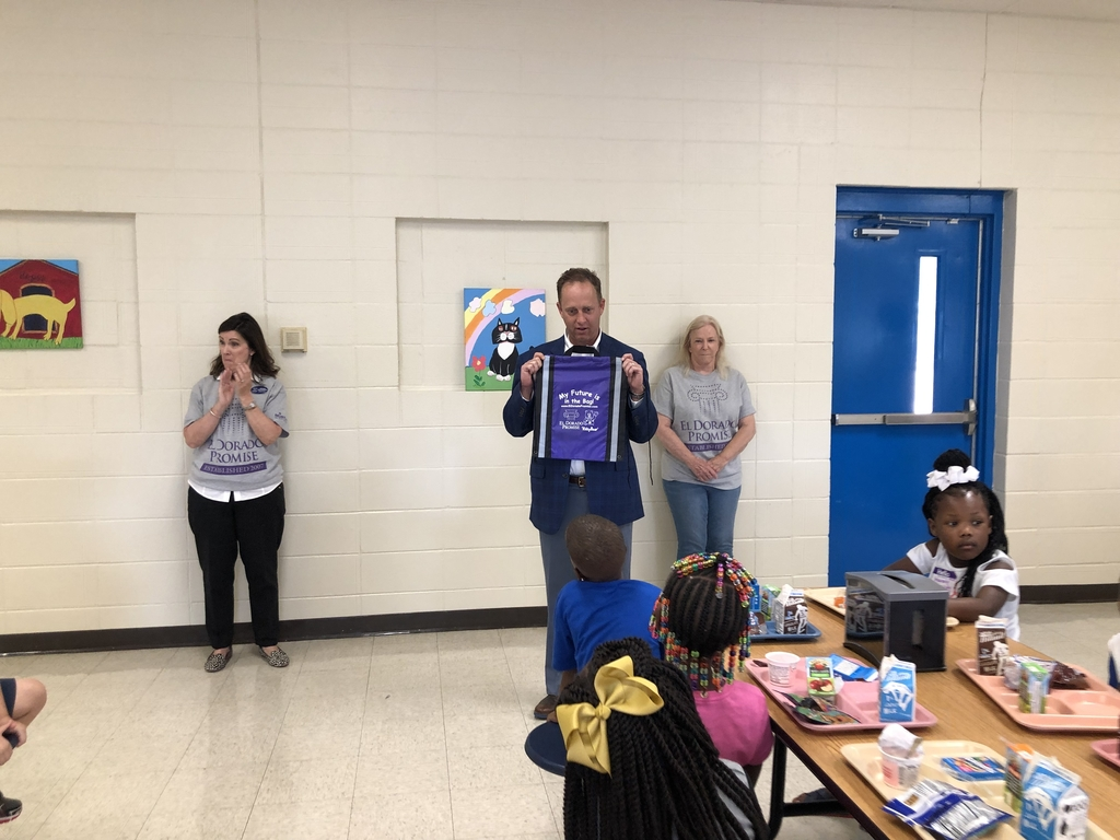 Rob Robinson of Simmons First Bank presents backpacks to students at Yocum Primary
